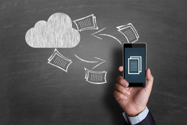 Cropped image of a businessman hand holding mobile phone on cloud computing icon drawn on chalkboard. He is transferring files from cloud network server.