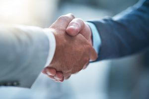 Cropped shot of two unrecognizable businessmen shaking hands after making a deal in the office