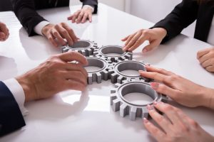 Group Of Businesspeople Joining Together Gears On Table At Workplace